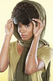 Portrait of an African American woman holding sunglasses with a stole over her head Royalty Free Stock Photos