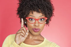 Portrait of an African American woman in retro glasses pointing upward over colored background Stock Photo