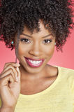 Portrait of an African American woman smiling over colored background Royalty Free Stock Image