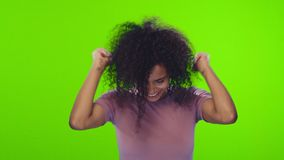 Portrait african american young woman with curly hair rejoices in victory. Attractive African American young woman clenches fists in victory gesture, exclaimed stock video footage
