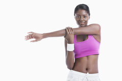Portrait of an African American young woman stretching arm over white background Stock Images