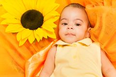 Portrait of African baby laying on sunflower cloth Royalty Free Stock Photo
