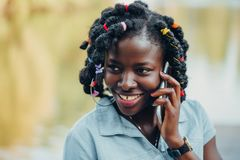 Portrait of an African beauty smiling young black woman in the park with a solar flare talking on the phone stock images