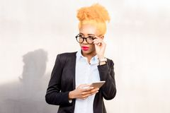Portrait of an african businesswoman on the gray background. Lifestyle portrait of an african businesswoman in glasses and casual suit standing with phone on the Royalty Free Stock Image