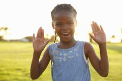 Portrait of African elementary school girl with hands raised royalty free stock photos