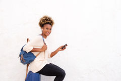 African female traveler sitting on suitcase with smart phone Stock Photography