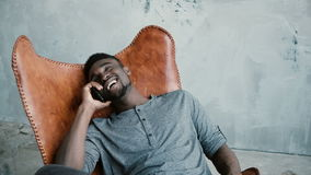 Portrait of African man sitting in the chair and talking on the Smartphone. Male is laughing at joke, having great time. Portrait of African man sitting in Royalty Free Stock Images