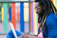Portrait of african man sitting outside with laptop. Urban work Concept Stock Images