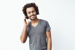 Portrait of african man in wireless headphones listening to streaming music service and enjoying the beat over white Royalty Free Stock Photography