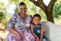 Portrait of african mother with child under tree. Stock Photos