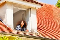 African girl enjoying morning in the open window. Portrait of African teenage girl enjoying morning in the open attic window royalty free stock images