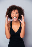 Portrait of african woman shouting. Over gray background Royalty Free Stock Photo