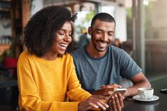 Young couple watching video on mobile phone stock images