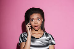 Portrait of a afro american woman gossiping on mobile phone. Portrait of a surprised afro american woman gossiping on mobile phone and looking at camera  over Royalty Free Stock Image