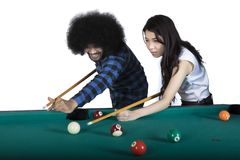 Two multiracial people playing billiards Royalty Free Stock Images