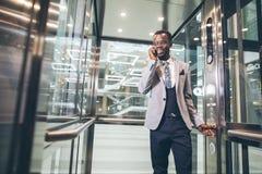 Afroamerican businessman in modern glass elevator talking on phone. Portrait of afroamerican businessman in modern glass elevator talking on phone Royalty Free Stock Photo
