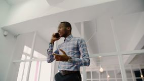 The portrait of afroamerican senior designer talking on phone in the corridor in the bright studio.  stock video footage