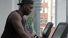 The portrait of afroamerican sportsman running on the race track on the gym. The professional looks to the monitor in front of him and holds the handles while stock video