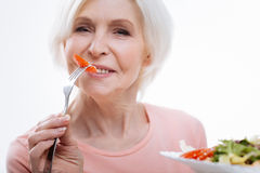 Portrait of aged female while eating tomato Royalty Free Stock Photo