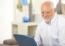 Portrait of aged man looking at laptop. Portrait of aged man at home looking at laptop computer screen, smiling royalty free stock photos
