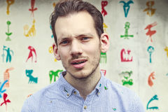 Portrait of a Aggravated Young Man. Standing against a colourful funky background Stock Images