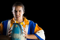 Portrait of aggressive female rugby player. Holding ball while standing against black background Stock Photo