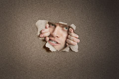 Portrait of a aggressive mid adult man peeking from ripped white paper hole Stock Images