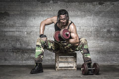 Portrait of aggressive muscle man lifting weights. On wall background Royalty Free Stock Photos