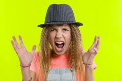 Portrait of an aggressive screaming teen girl over yellow studio background royalty free stock photos