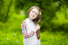 Portrait of agirl in the park on a background of green trees Stock Image