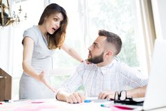 Agitated Businesswoman. Portrait of agitated businesswoman looking shocked while explaining something to handsome colleague sitting at desk in office stock photo