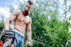 Portrait of agressive athletic man with chainsaw getting ready. For fire wood cutting Royalty Free Stock Photography