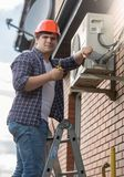 Portrait of young air conditioner engineer checking conditioning system. Portrait of air conditioner engineer checking conditioning system Stock Photos