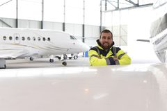 Portrait of an aircraft mechanic in a hangar with jets at the ai. Rport - Checking the aircraft for safety and technical function Royalty Free Stock Photography