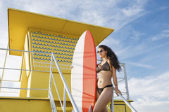 Portrait of alluring Latin women holding surfboard with copy space for your brand while standing on the lifeguard house Royalty Free Stock Photo