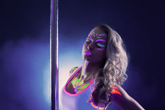Portrait of alluring pole dancer with neon makeup. Portrait of alluring pole dancer posing with neon makeup Royalty Free Stock Image