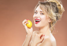 Portrait of Alluring Sexy Caucasian Blond Girl Biting Lemon Stock Photo