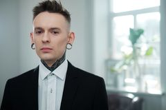 Portrait of alternative model with earplugs and tattoo royalty free stock images