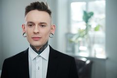 Portrait of alternative model with earplugs and tattoo stock images