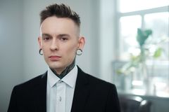 Portrait of alternative model with earplugs and tattoo stock photo