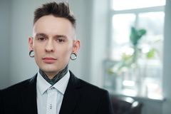 Portrait of alternative model with earplugs and tattoo.  royalty free stock photos