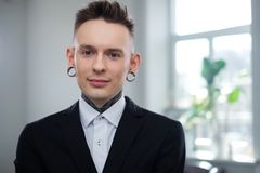 Portrait of alternative model with earplugs and tattoo.  stock photo