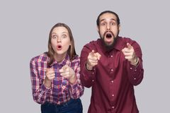 Portrait of amazed bearded man and woman in casual style standing, pointing and looking at camera with surprised unbelievable royalty free stock photography