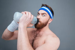 Portrait amazed bearded sportsman drinking water Royalty Free Stock Images