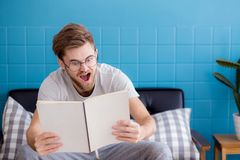 Portrait of amazed casual man reading book on living room. The portrait of amazed casual man reading book on living room Royalty Free Stock Photos