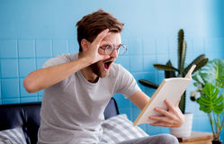Portrait of amazed casual man reading book. On living room Stock Photos