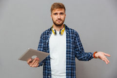 Portrait of amazed frustrated man using tablet computer. Over gray background Royalty Free Stock Image