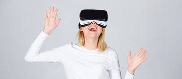 Portrait of an amazed girl using a virtual reality headset isolated on grey background. Happy woman exploring augmented royalty free stock photography