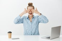 Portrait of amazed good-looking female entrepreneur in office, covering eyes with palms and waiting impatiently for. Surprise while sitting near laptop and Royalty Free Stock Photography