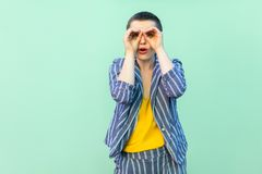 Portrait of amazed handsome beautiful short hair young stylish woman in casual striped suit standing with binoculars hands on eyes royalty free stock image